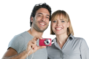 Happy joyful couple taking pictures with digital camera isolated on white background